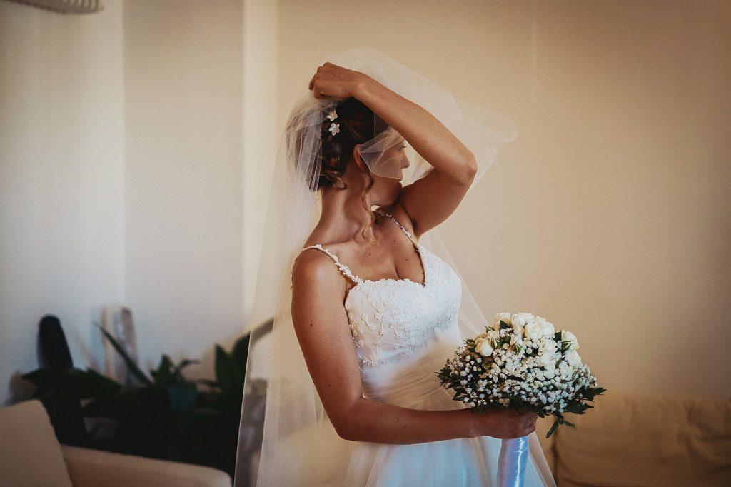 la sposa si aggiusta il velo prima di uscire di casa per andare al matrimonio a il conventino di mentana