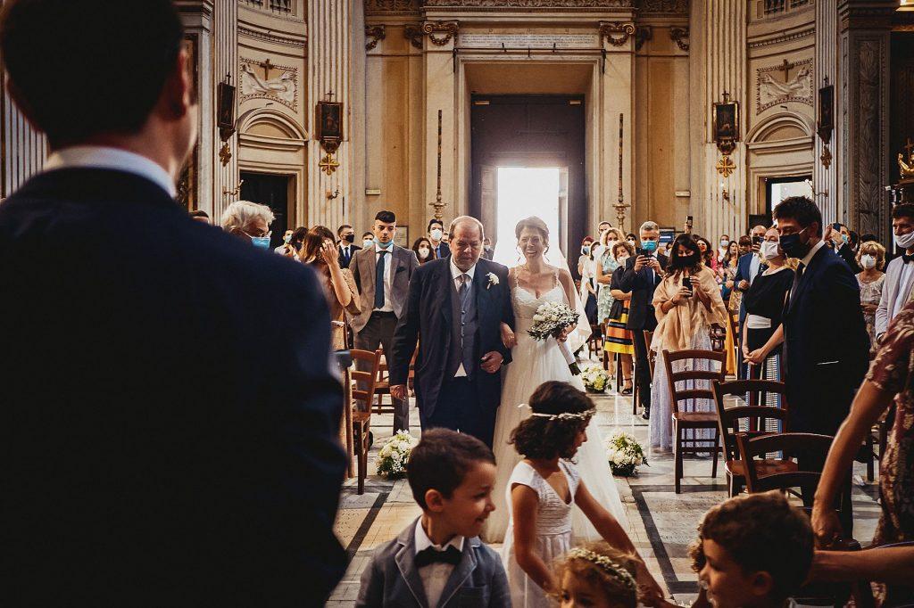 la sposa entra in chiesa sotto il braccio del papˆ, mentre lo sposo lÕaspetta e la guarda