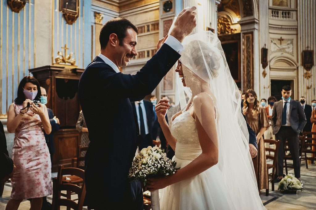 gli sposi si incontrano in chiesa, lo sposo alza il velo della sposa e la saluta