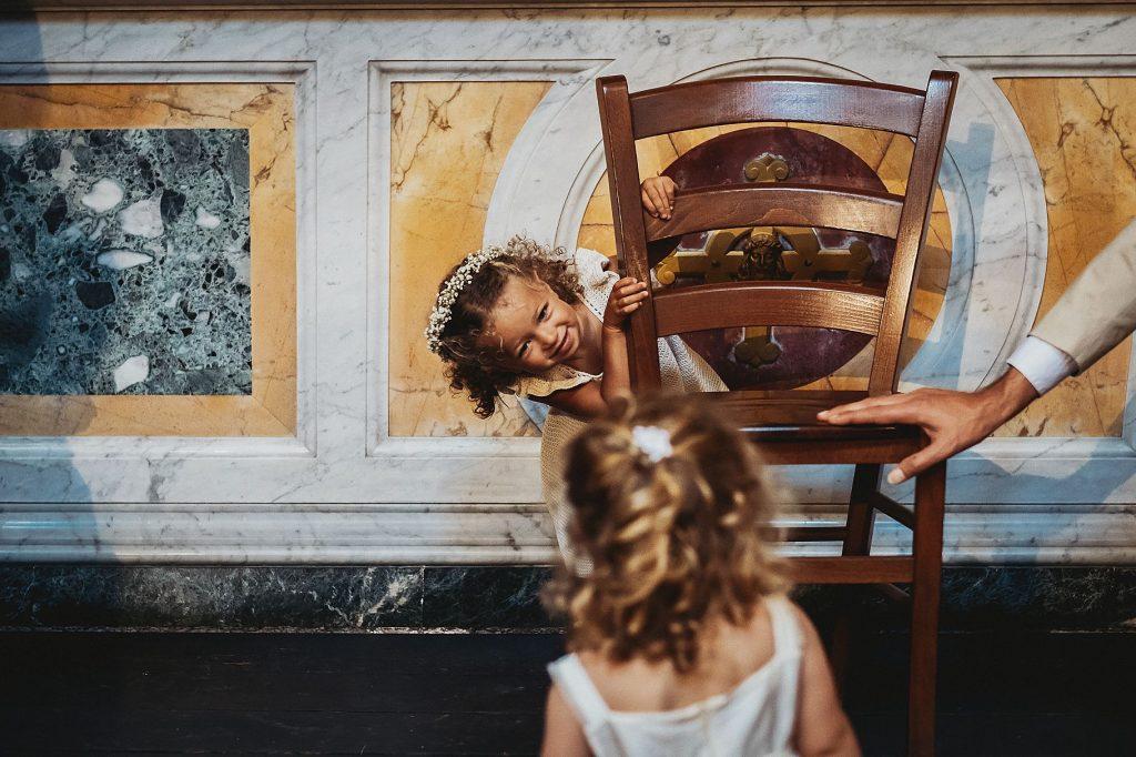 bambine e piccole damigelle che giocano a nascondino in chiesa durante la cerimonia