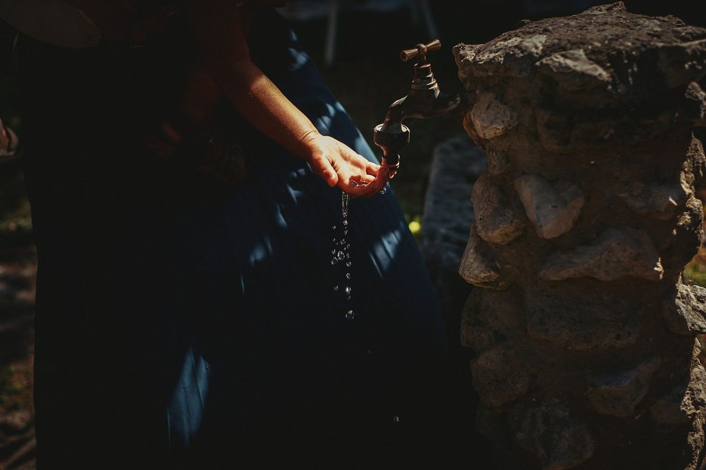 dettaglio della mano di un bambino al matrimonio a il conventino che gioca ad una fontana