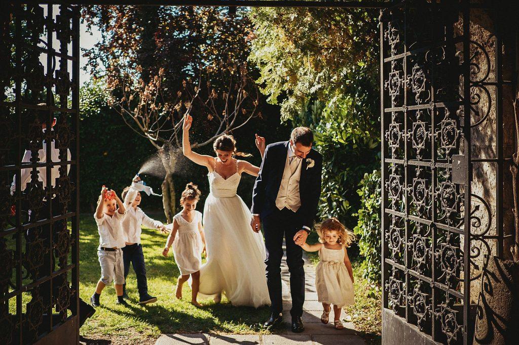 gli sposi con bambini e pistole ad acqua mentre entrano nel chiostro de Il Conventino per il taglio della torta