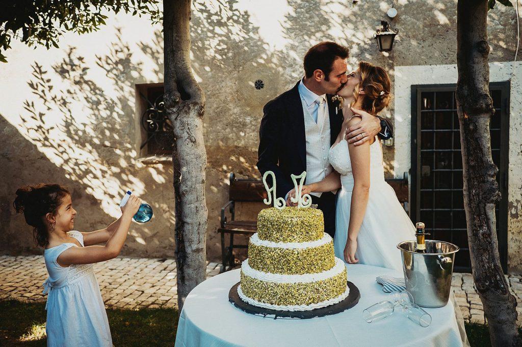 gli sposi si baciano al taglio della torta nel chiostro de Il Conventino mentre una bambina cerca di bagnargli con una pistola ad acqua