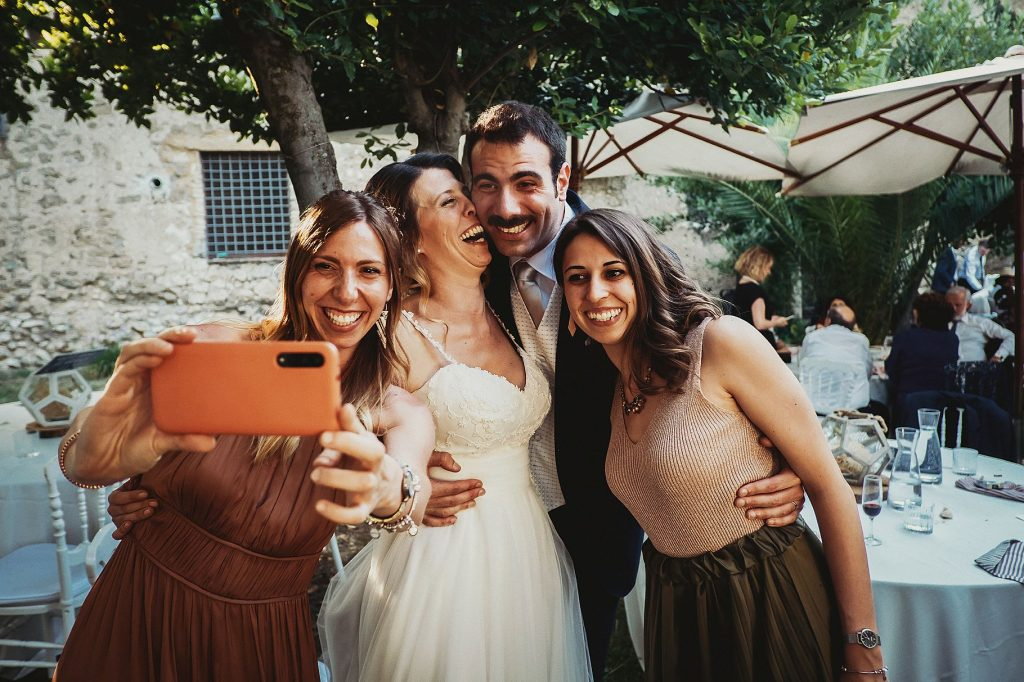 selfie degli sposi con invitati tra i tavoli del pranzo di matrimonio a il conventino