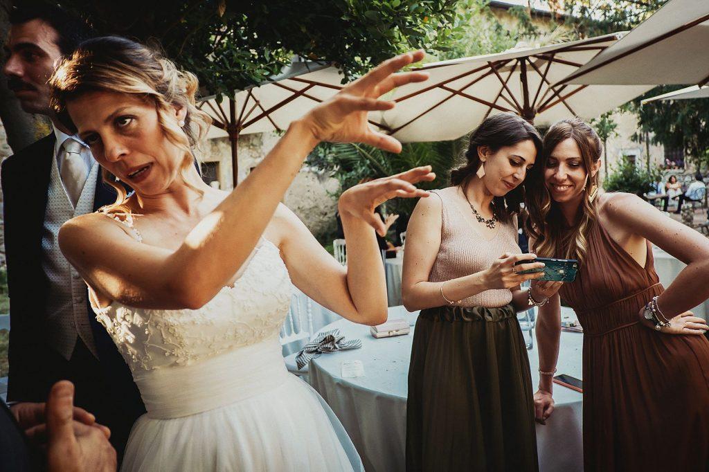 due amiche della sposa che guardano il telefono mentre la sposa gesticola in primo piano
