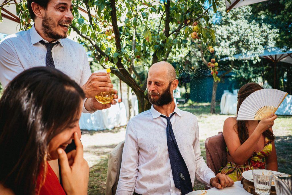 invitati che giocano con le pistole ad acqua al matrimonio e prendono contatti per prenotare fotografo matrimonio
