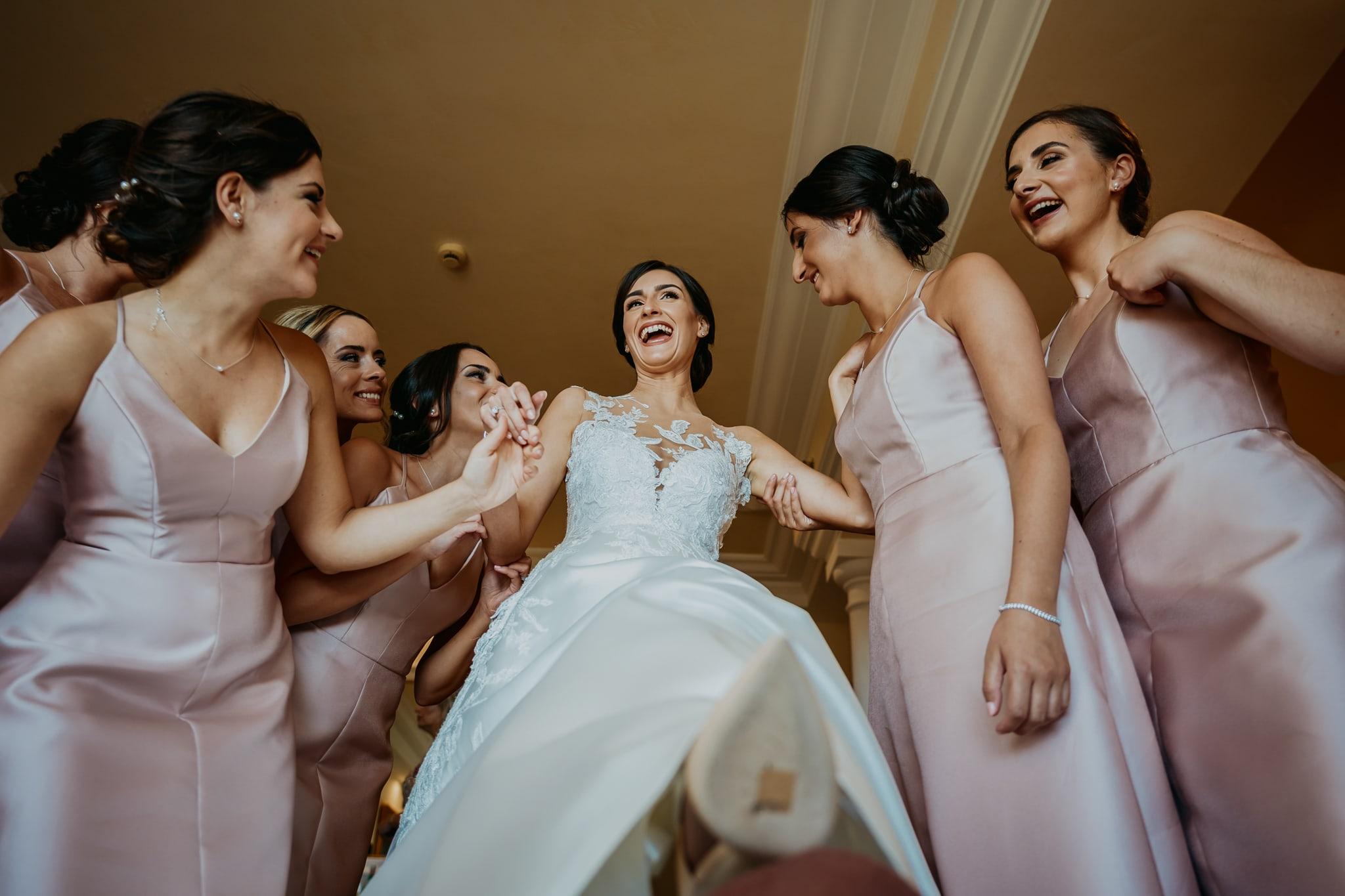 fotografi matrimonio roma, sposa che ride con damigelle durante la preparazione