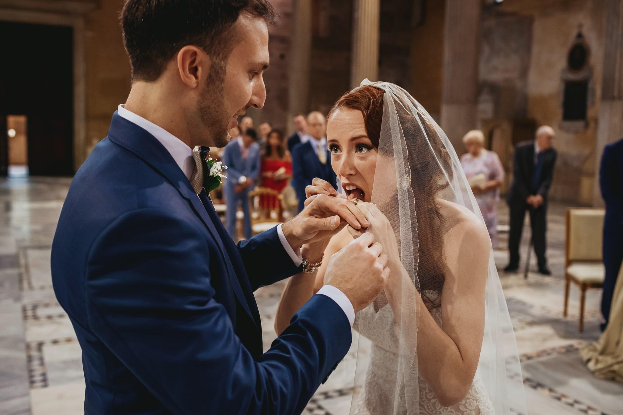 foto divertente fatta dai fotografi di matrimonio a  roma della sposa che lecca la fede prima dello scambio degli anelli