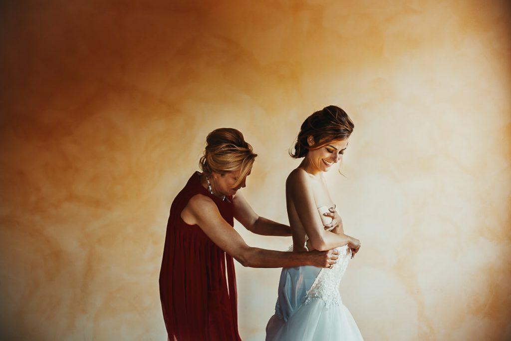 recensioni fotografo di matrimoni, la sposa indossa il vestito aiutata dalla mamma