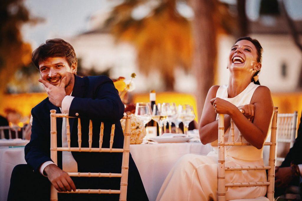 recensioni fotografo di matrimoni, sposi al ricevimento che ridono seduti al loro tavolo
