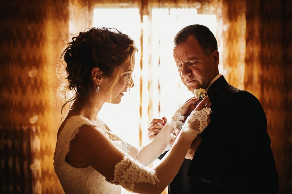 recensioni fotografo di matrimoni, sposa aiuta il papà ad indossare il fiore all'occhiello