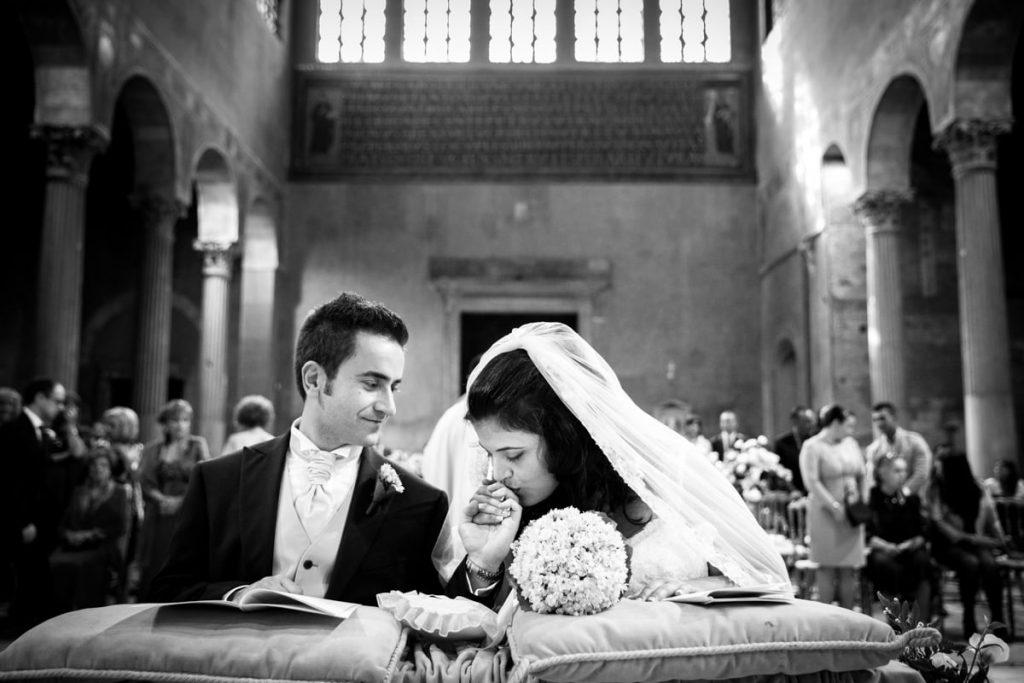 recensioni fotografo di matrimoni, la sposa bacia la mano allo sposo in chiesa