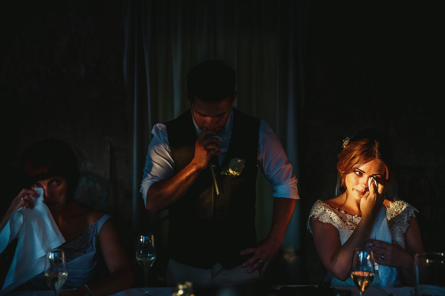 foto del fotografo di matrimonio in italia in cui un raggio di sole illumina il viso emozionato della sposa durante il discorso dello sposo al ricevimento