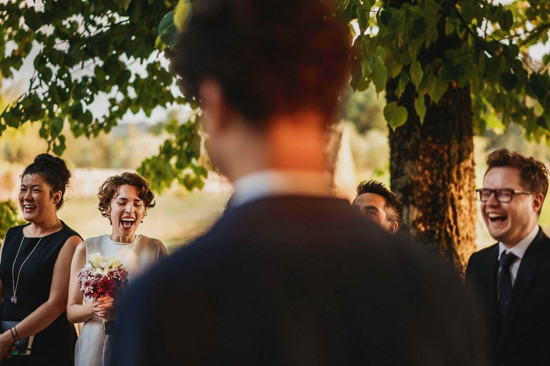 il fotografo di matrimonio in italia ha colto gli sposi e testimoni che ridono durante la cerimonia simbolica di un matrimonio all'aperto