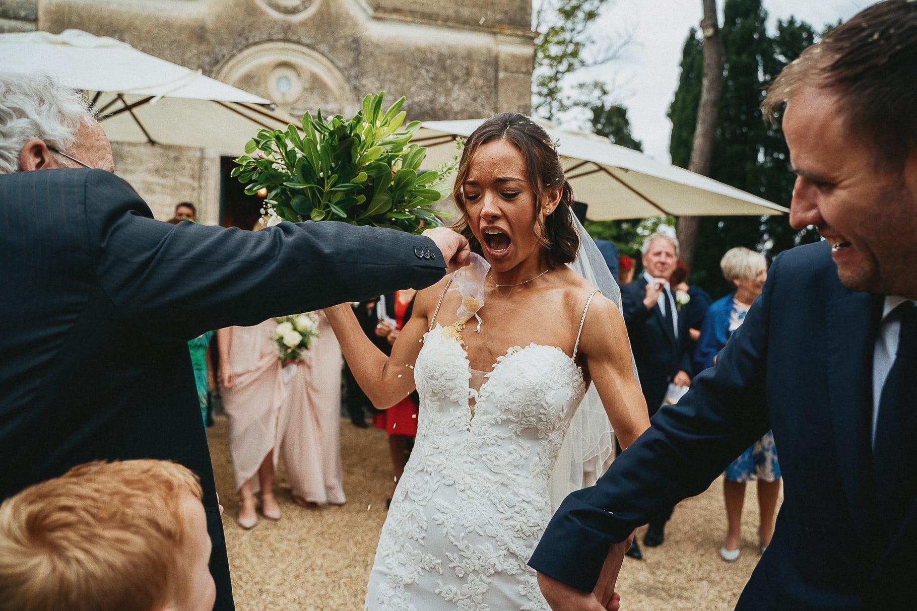 gli sposi escono mano per la mano dalla chiesa e gli invitati lanciano il riso in una foto del fotografo di matrimonio in italia