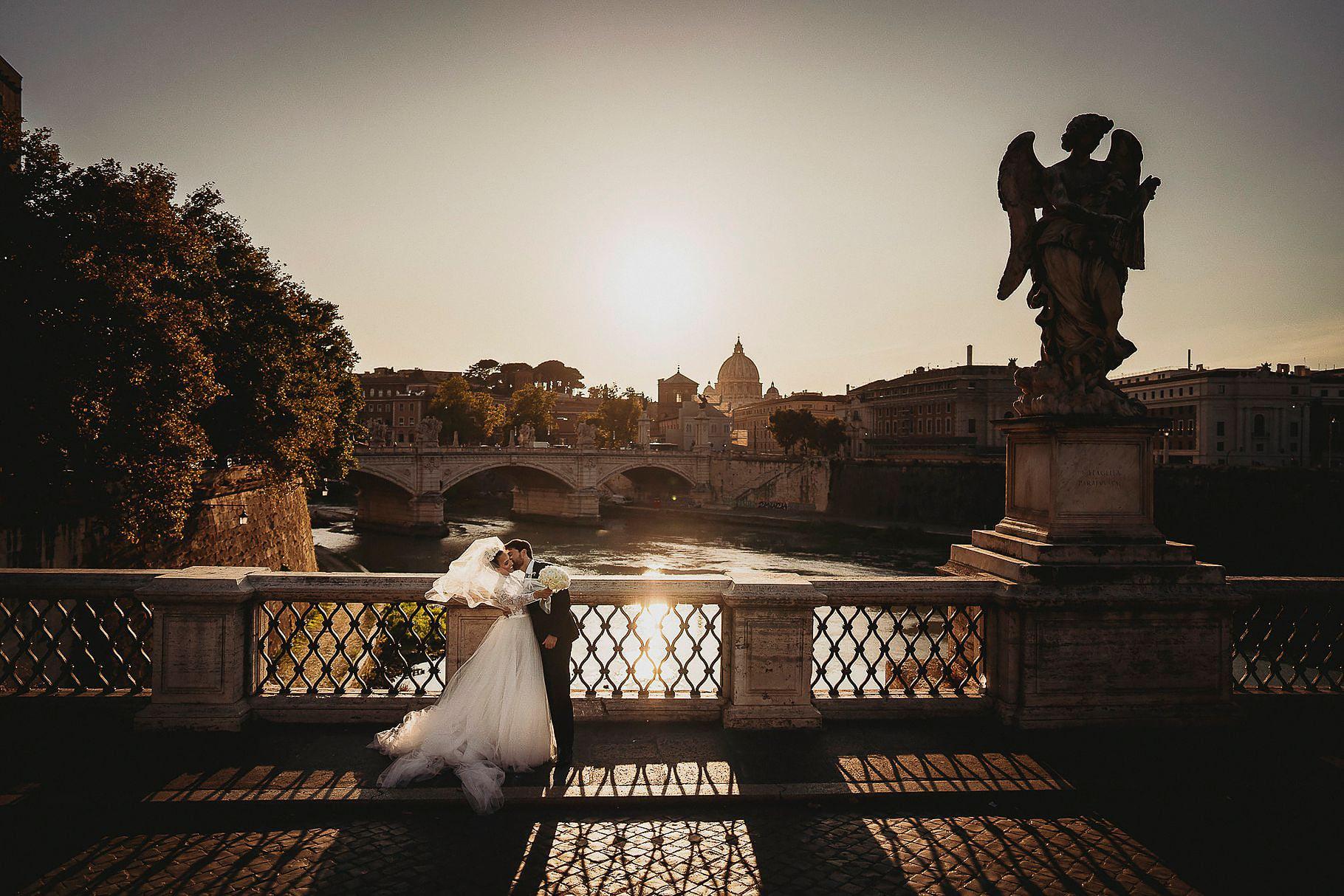 coppia di sposi fotografati dal fotografo di matrimonio in italia sul ponte dell'angelo a roma con il tevere e la cupola di san pietro sullo sfondo