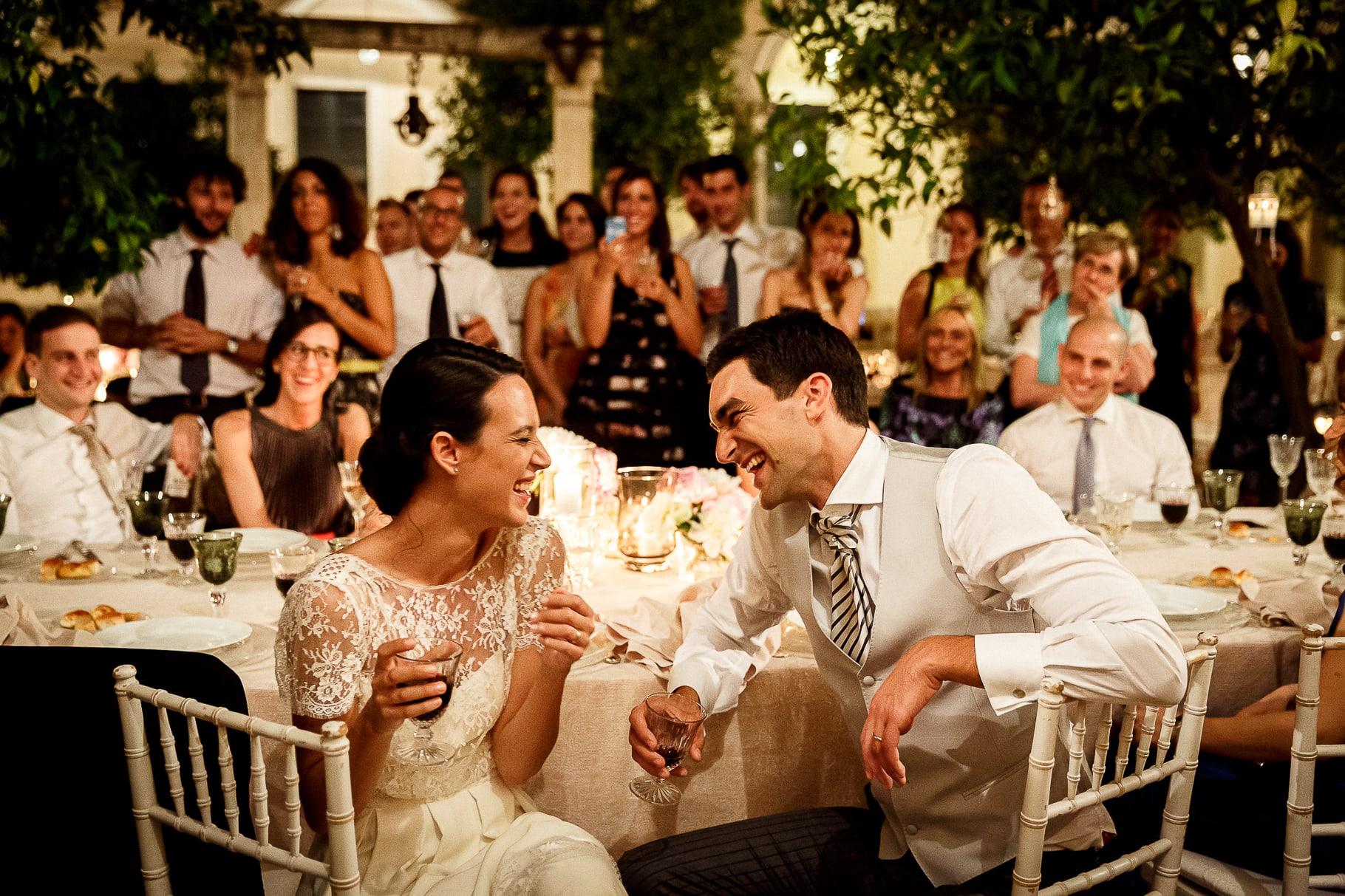 gli sposi ridono e brindano con gli invitati durante il ricevimento di matrimonio al chiostro dell'istituto degli studi romani a roma