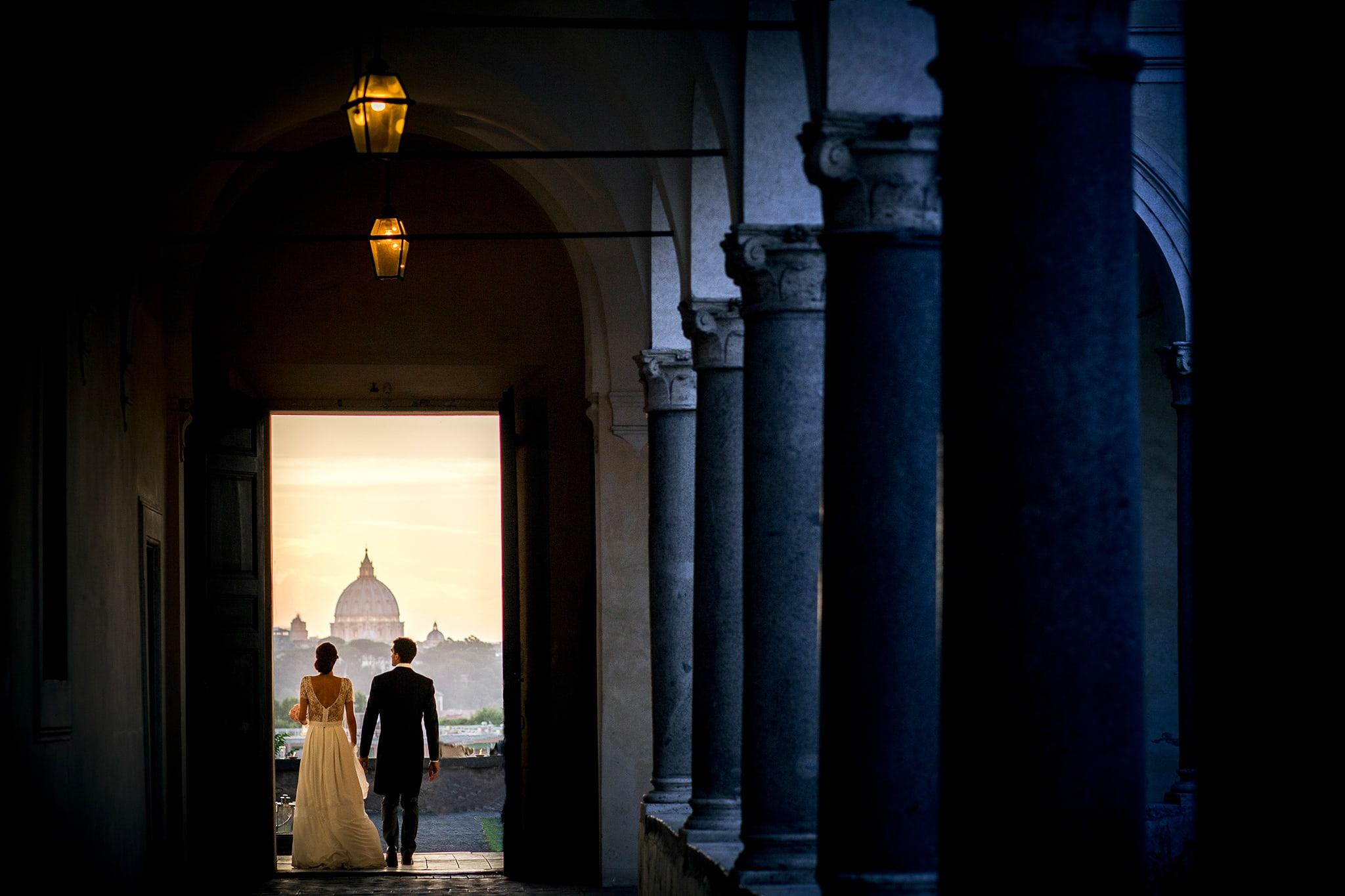 La sposa e lo sposo si tengono per mano nel chiostro dellÕistituto degli studi romani allÕaventino con il cupolone sullo sfondo immagine colta dal miglior fotografo matrimonio roma