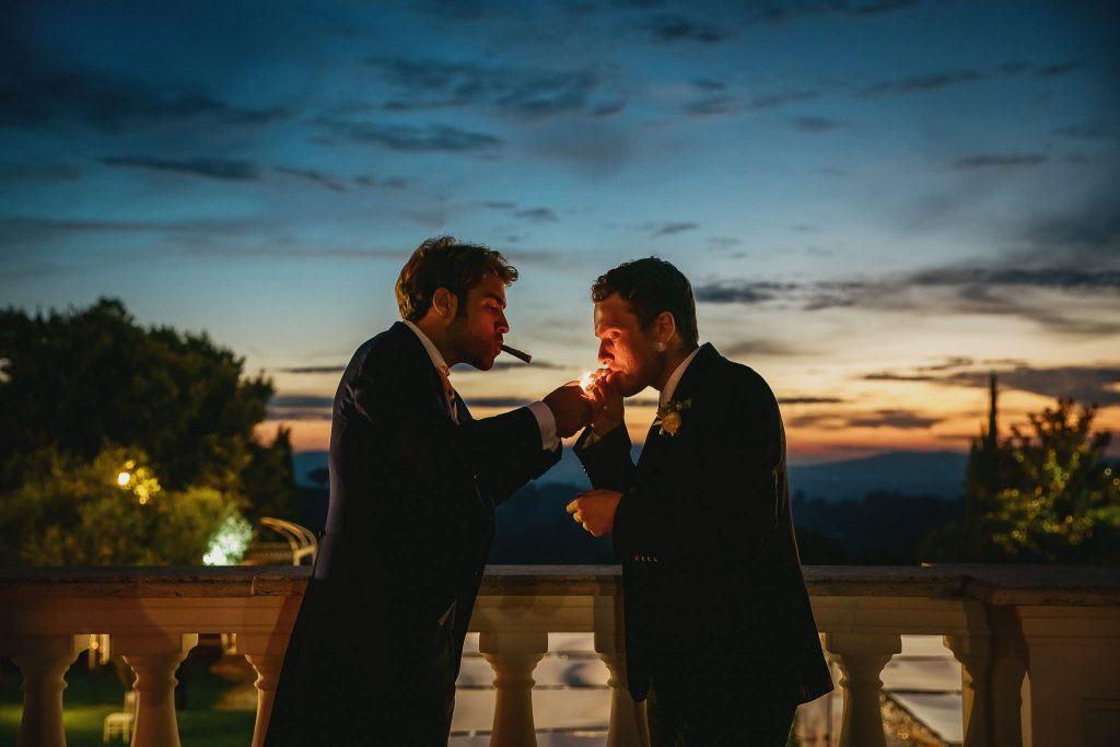 lo sposo e il testimone di nozze fumano un sigaro al tramonto ecco un esempio di come fotografare matrimoni in luce ambiente