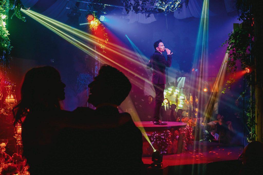 cantante alla festa di matrimonio con luci colorate e persone in primo piano