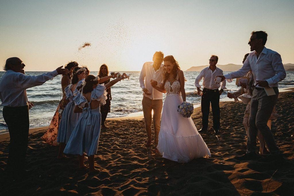 fotografare matrimoni in luce ambiente sulla spiaggia al tramonto lancio del riso alla fine della cerimonia simbolica