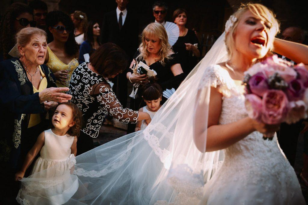 bambina che tira il velo della sposa un esempio di fotografia documentaria matrimonio