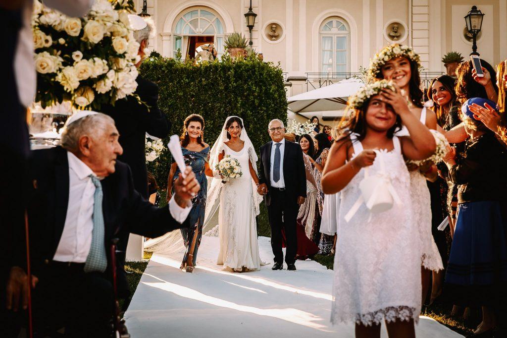 fotografia documentaria di matrimonio durante l'ingresso della sposa con mamma e papà al matrimonio ebraico a villa miani