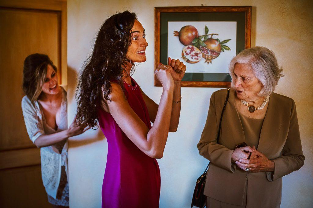 la nonna della sposa, la sorella della sposa e la sposa in una fotografia documentaria di matrimonio durante la preparazione