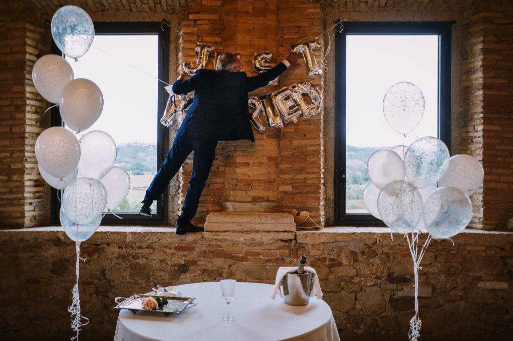un ospite del matrimonio arrampicato su un davanzale per sistemare i palloncini