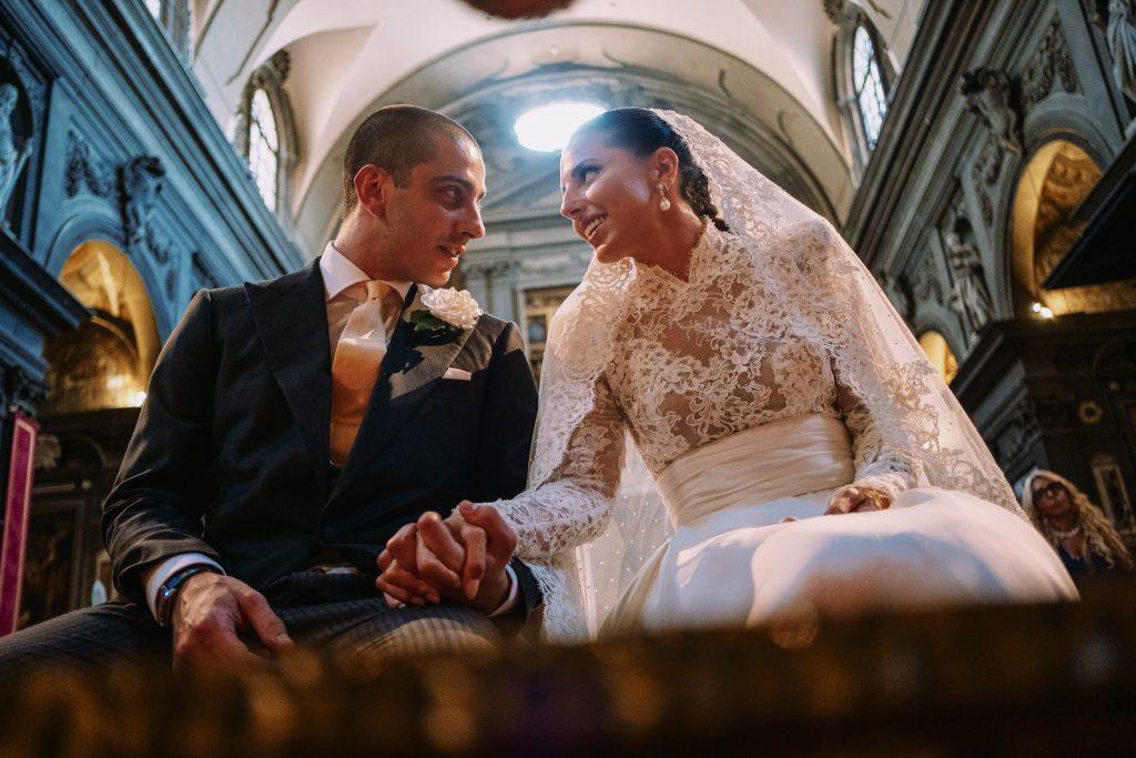 lo-sposo-e-la-sposa-si-tengono-la-mano-in-chiesa-durante-il-loro-matrimonio-e-si-guardano-con-amore-seduti-vicino-allo-altare
