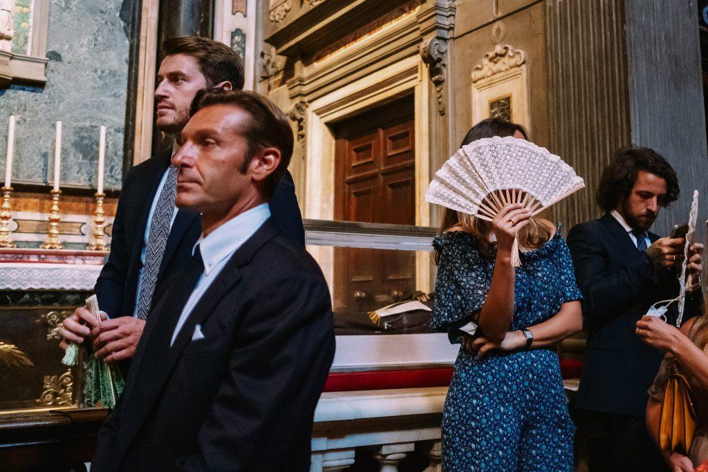 invitati-ad-un-matrimonio-ascoltano-la-cerimonia-con-interesse-una-invitata-non-vuole-farsi-fotografare-e-si-sventola-con-un-ventaglio-perche-ha-caldo