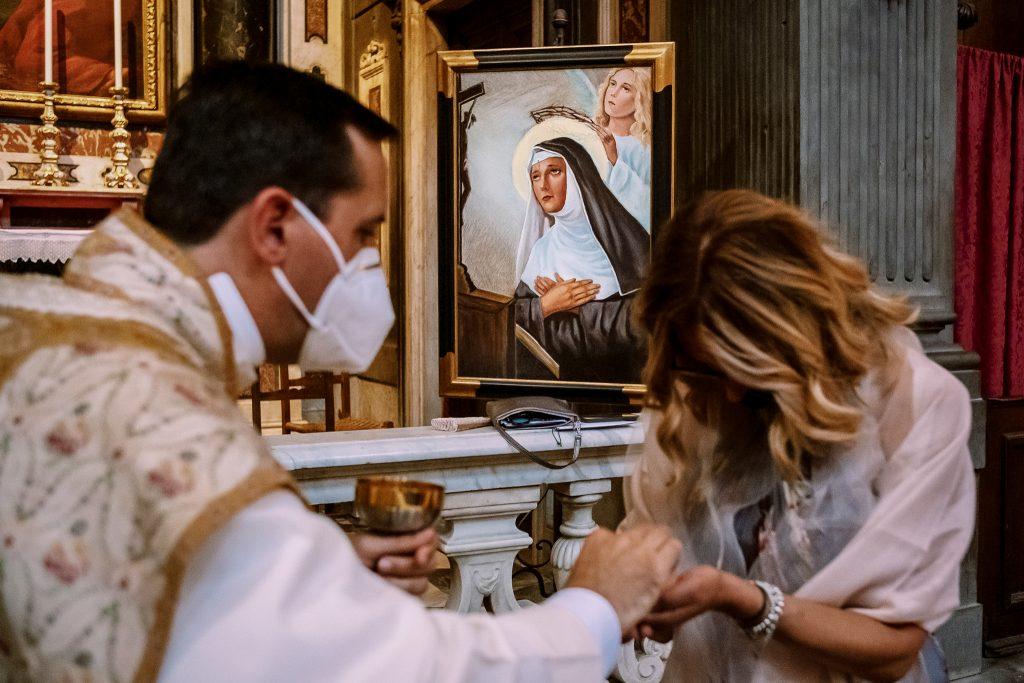 invitata-ad-un-matrimonio-a-firenze-riceve-la-comunione-con-dietro-un-ritratto-di-santa