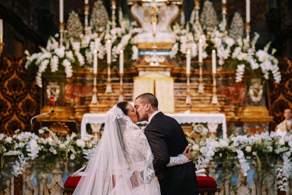 sposi-si-baciano-dopo-lo-scambio-degli-anelli-in-chiesa-al-loro-matrimonio-a-firenze-davanti-allo-altare