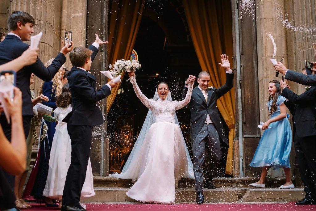 lo-sposo-e-la-sposa-escono-dalla-chiesa-dopo-la-cerimonia-per-il-lancio-del-riso-e-tutti-gli-invitati-li-salutano