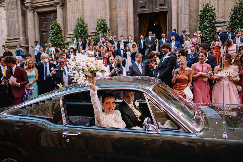 gli-sposi-vanno-via-con-la-macchina-dopo-la-cerimonia-del-loro-matrimonio-a-firenze-mentre-la-sposa-solleva-il-suo-bouquet-in-aria-fuori-dal-finestrino