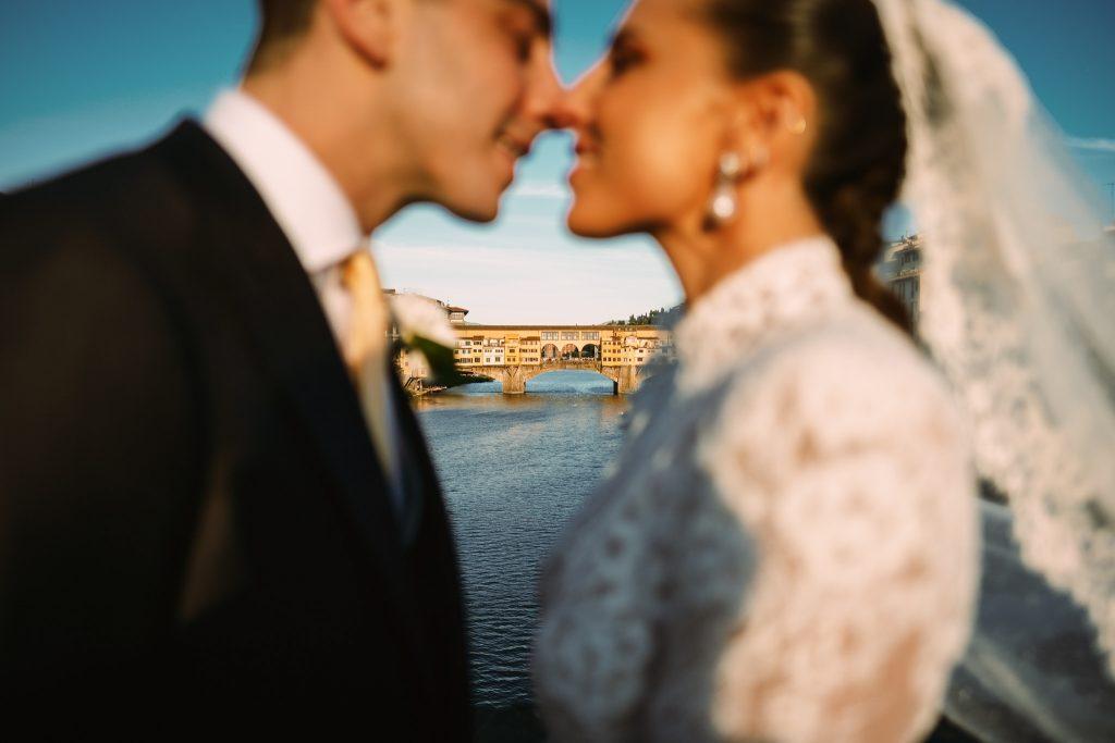 gli-sposi-si-baciano-davanti-ponte-vecchio-nel-giorno-del-loro-matrimonio-a-firenze