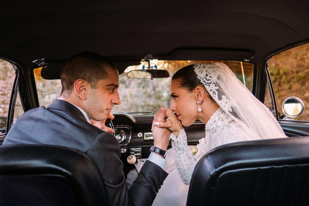 lo-sposo-e-la-sposa-in-macchina-dopo-la-cerimonia-del-loro-matrimonio-a-firenze-si-baciano-e-si-guardano-intensamente