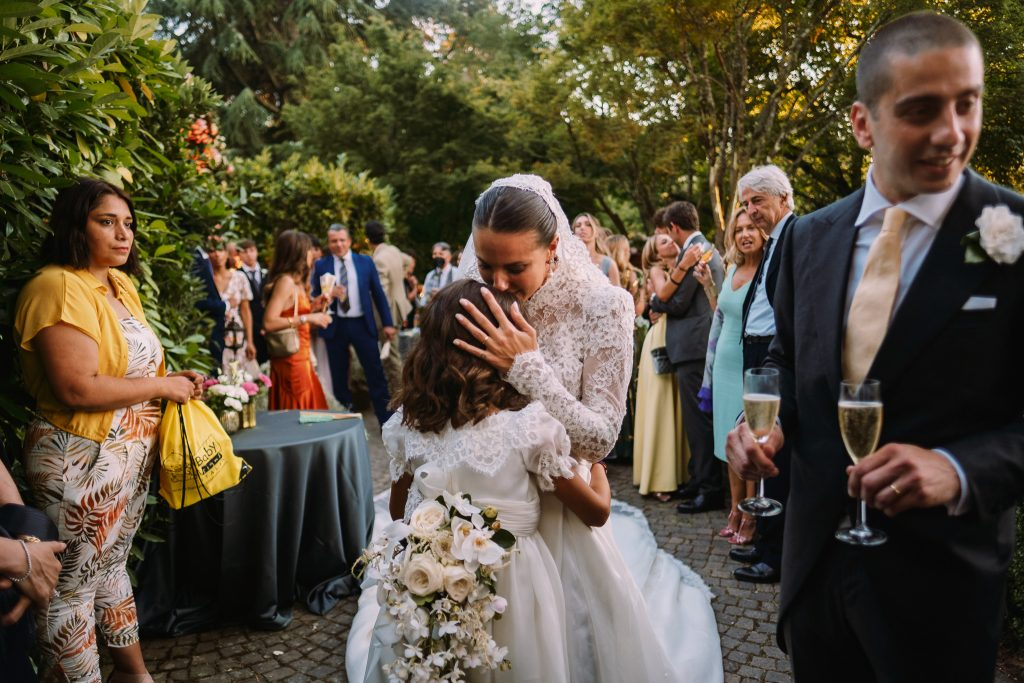 gli-sposi-arrivano-allo-aperitivo-e-salutano-gli-invitati-mentre-la-sposa-bacia-la-sua-nipotina-che-ha-portato-le-fedi