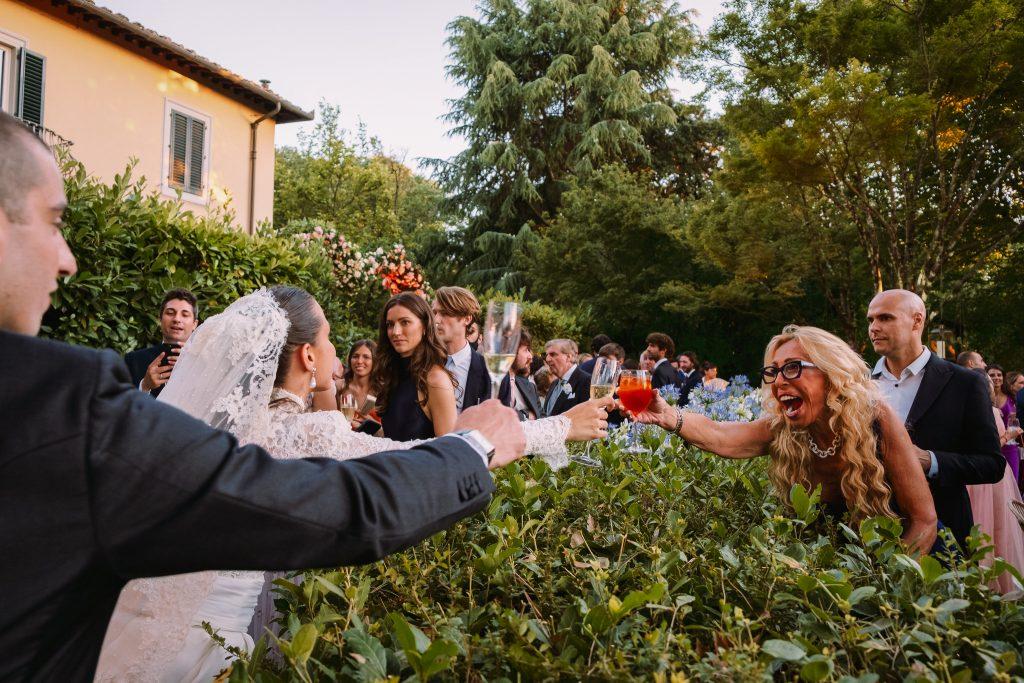 lo-sposo-e-la-sposa-brindano-con-la-mamma-della-sposa-durante-aperitivo-del-loro-matrimonio-di-firenze-mentre-la-mamma-sorride