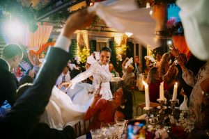 lo-sposo-e-la-sposa-entrano-nella-sala-del-ricevimento-del-loro-matrimonio-mentre-tutti-gli-invitati-sventolano-i-tovaglioli-per-accoglierli