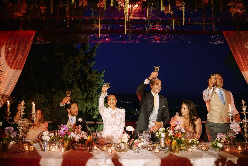 gli-sposi-alzano-i-calici-per-brindare-con-i-loro-invitati-per-il-loro-matrimonio-a-firenze-durante-il-ricevimento-dietro-al-tavolo-imperiale