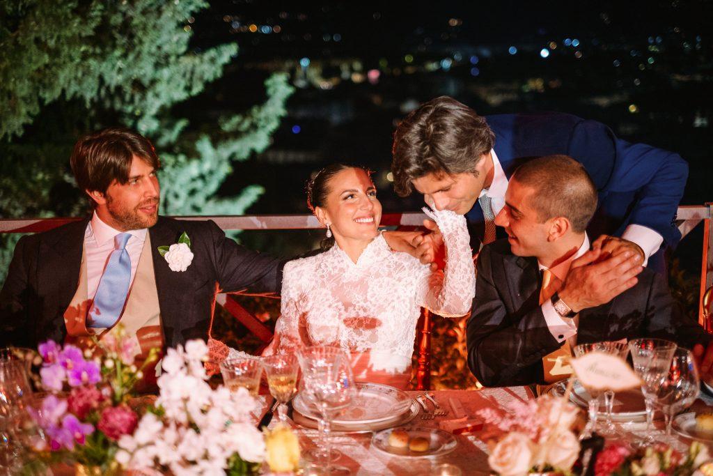 la-sposa-fa-una-carezza-ad-un-testimone-durante-il-ricevimento-di-matrimonio-e-lo-sposo-ed-il-testimone-li-guardano-e-sorridono