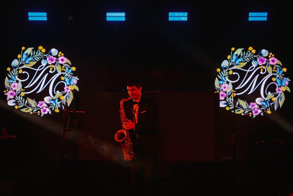 un-sax-suonato-da-un-saffonista-sul-palco-della-festa-per-gli-sposi-durante-il-ricevimento-del-loro-matrimonio-a-firenze-con-luci-colorate-e-proiezione-del-loro-logo
