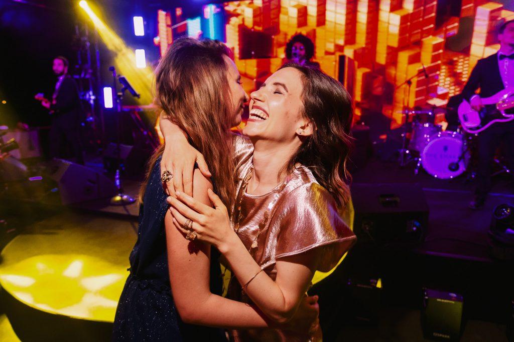 invitate-al-matrimonio-ballano-davanti-al-palco-con-la-musica-durante-il-ricevimento-del-matrimonio-dei-loro-amici-mentre-si-abbracciano