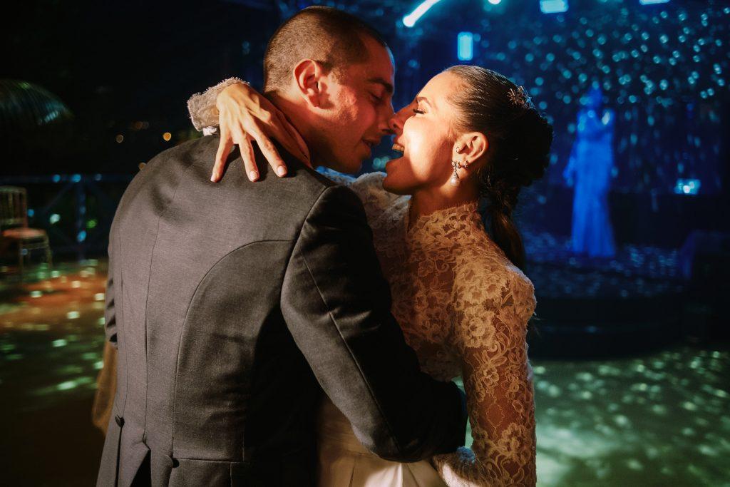 lo-sposo-e-la-sposa-ballano-al-ricevimento-del-loro-matrimonio-con-luci-colorate-mentre-si-abbracciano-appassionatamente