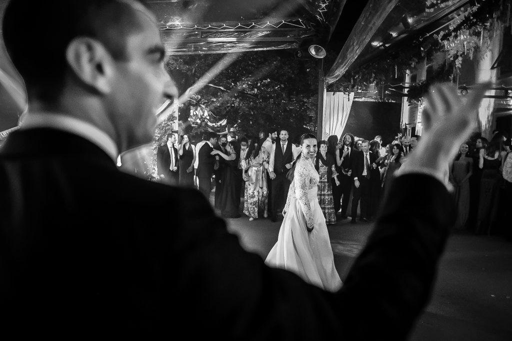 lo-sposo-invita-la-sposa-e-gli-invitati-a-ballare-durante-il-ricevimento-di-nozze-con-luci-colorate-e-la-sposa-lo-guarda-ridendo
