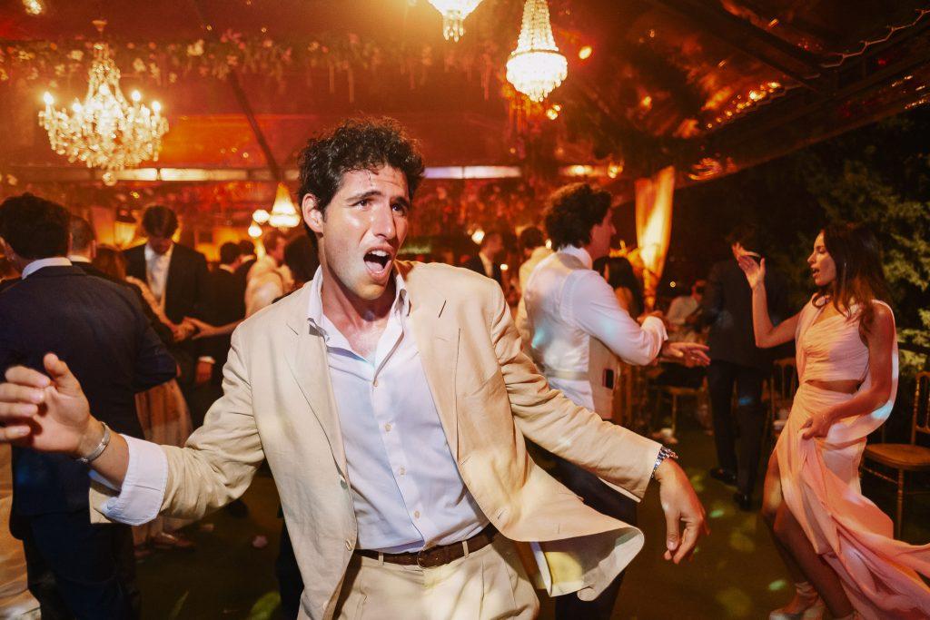 invitato-con-giacca-chiara-e-completo-chiaro-balla-animatamente-durante-un-ricevimento-di-matrimonio-a-firenze-con-luci-colorate-sullo-sfondo-con-posa-che-assomiglia-a-john-travolta