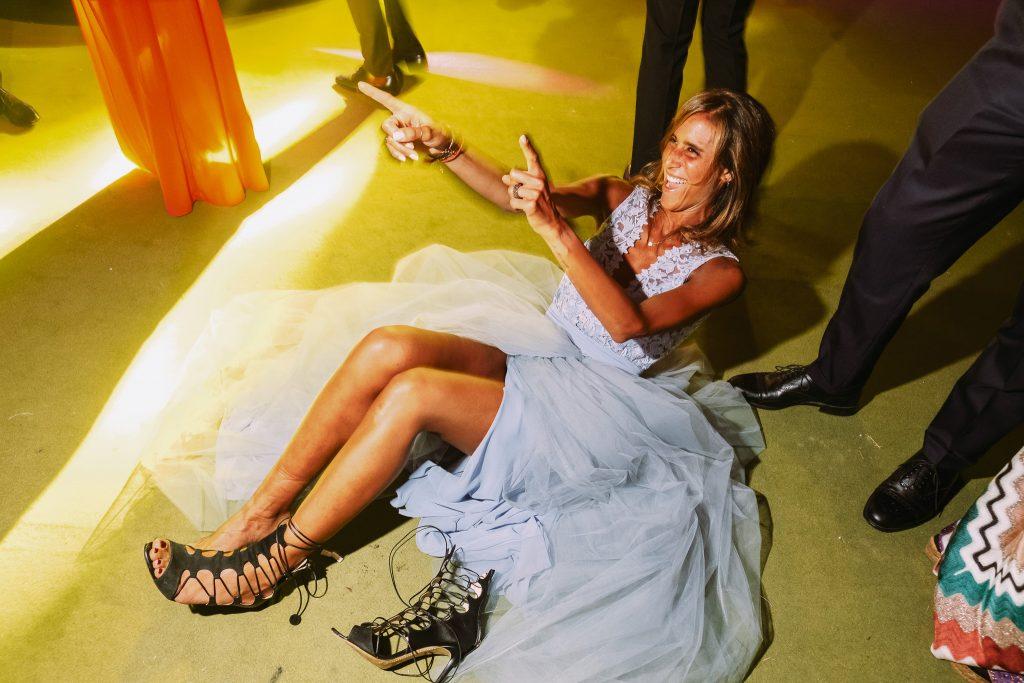 invitata-ad-un-matrimonio-seduta-per-terra-mentre-si-toglie-le-scarpe-per-ballare-insieme-agli-sposi-e-saluta-il-suo-fidanzato