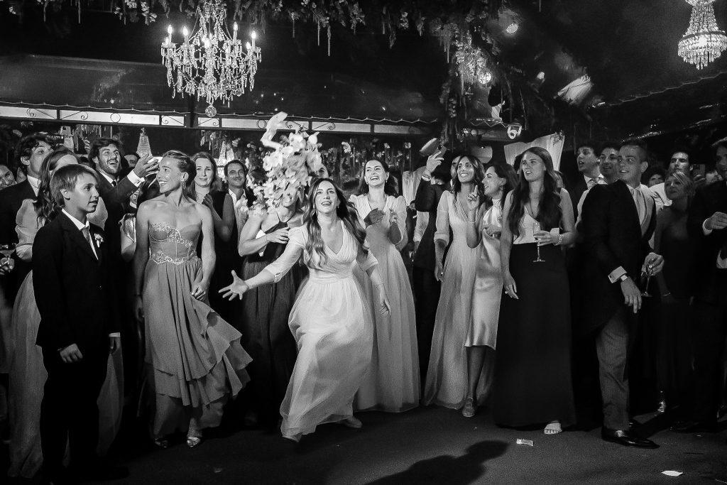 una-testimone-prende-il-bouquet-durante-il-lancio-del-bouquet-in-un-ricevimento-di-matrimonio-con-gli-invitati-che-guardano-e-luci-colorate