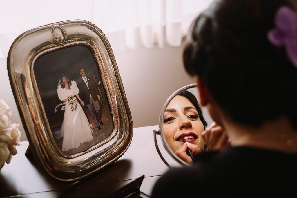 la sposa si trucca davanti allo specchio vicino la foto del matrimonio dei propri genitori